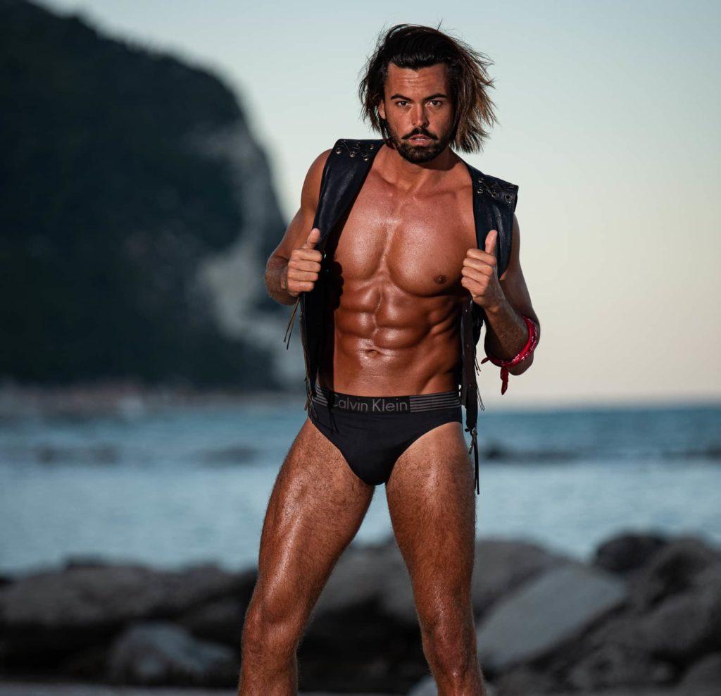 modello fitness con addome scolpito in spiaggia e intimo calvin klein