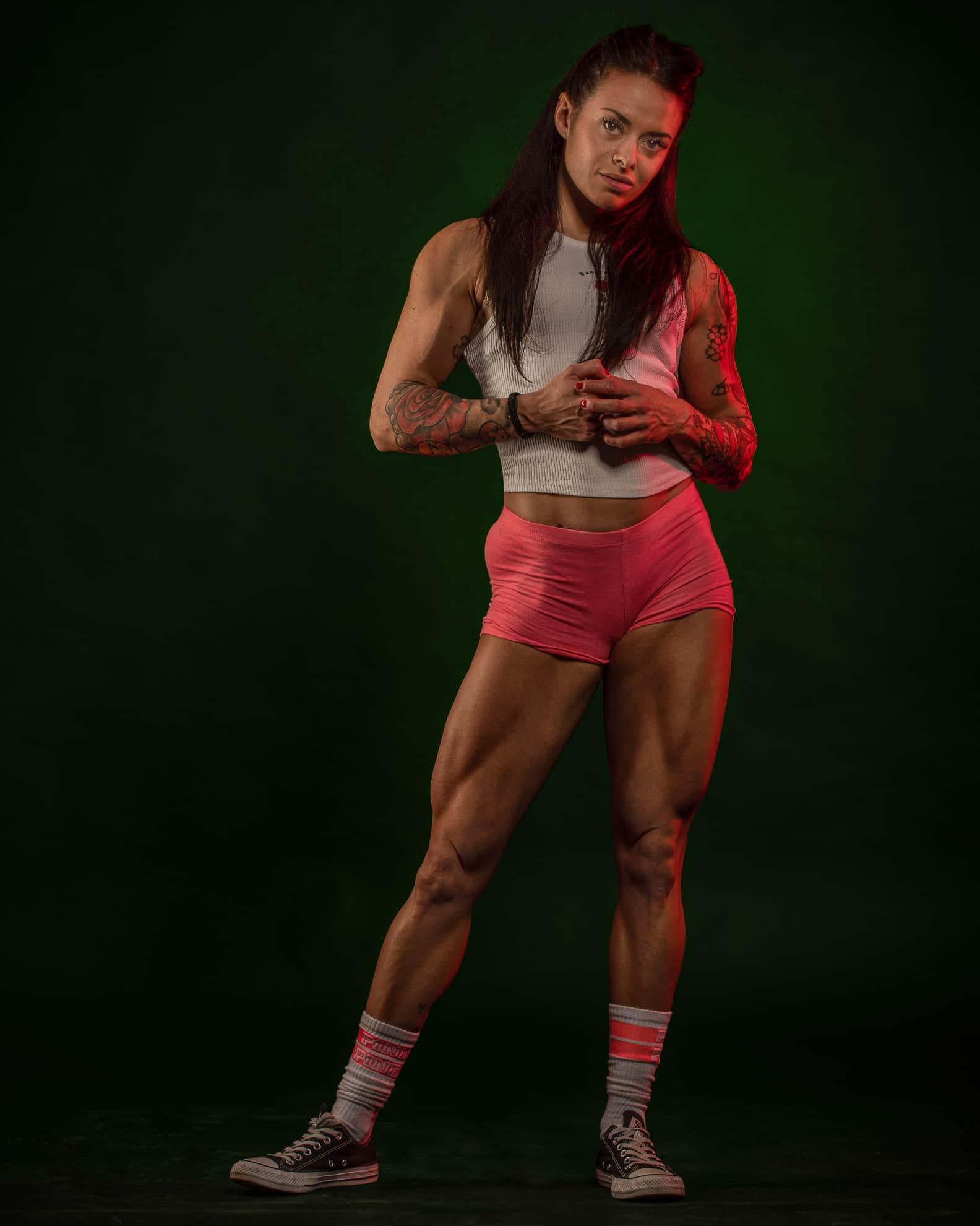 ragazza con gambe muscolose in studio fotografico con luce verde sullo sfondo