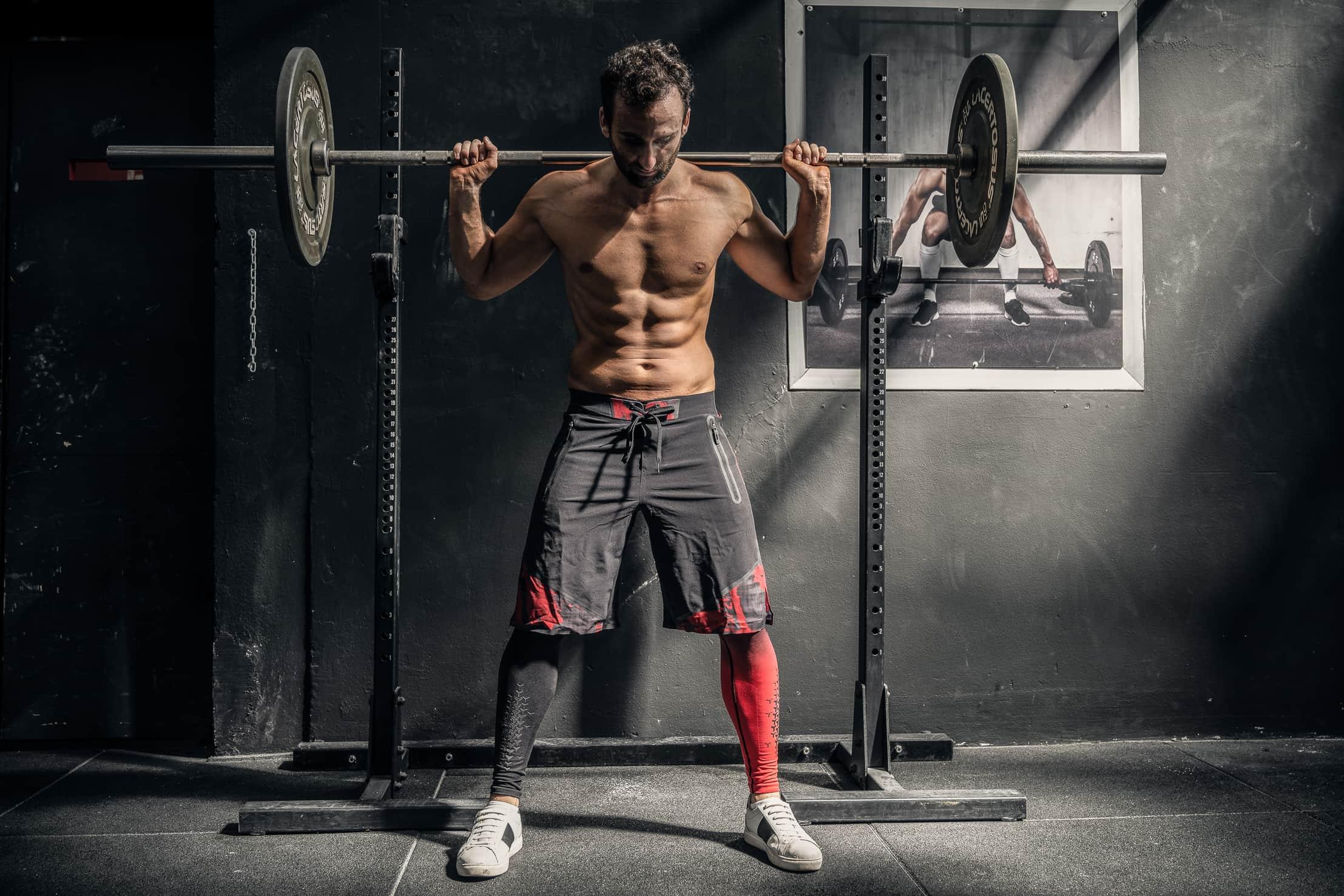 fotografofitness ragazzo muscoloso allo squat in palestra