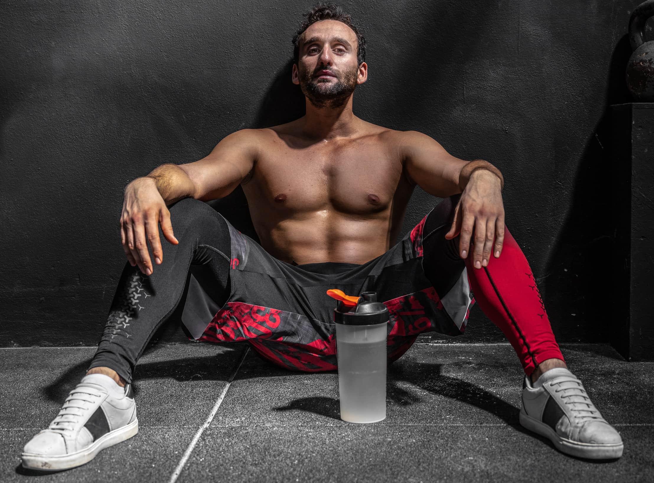 fotografofitness servizio fitness in palestra ragazzo a torso nudo seduto per terra in palestra