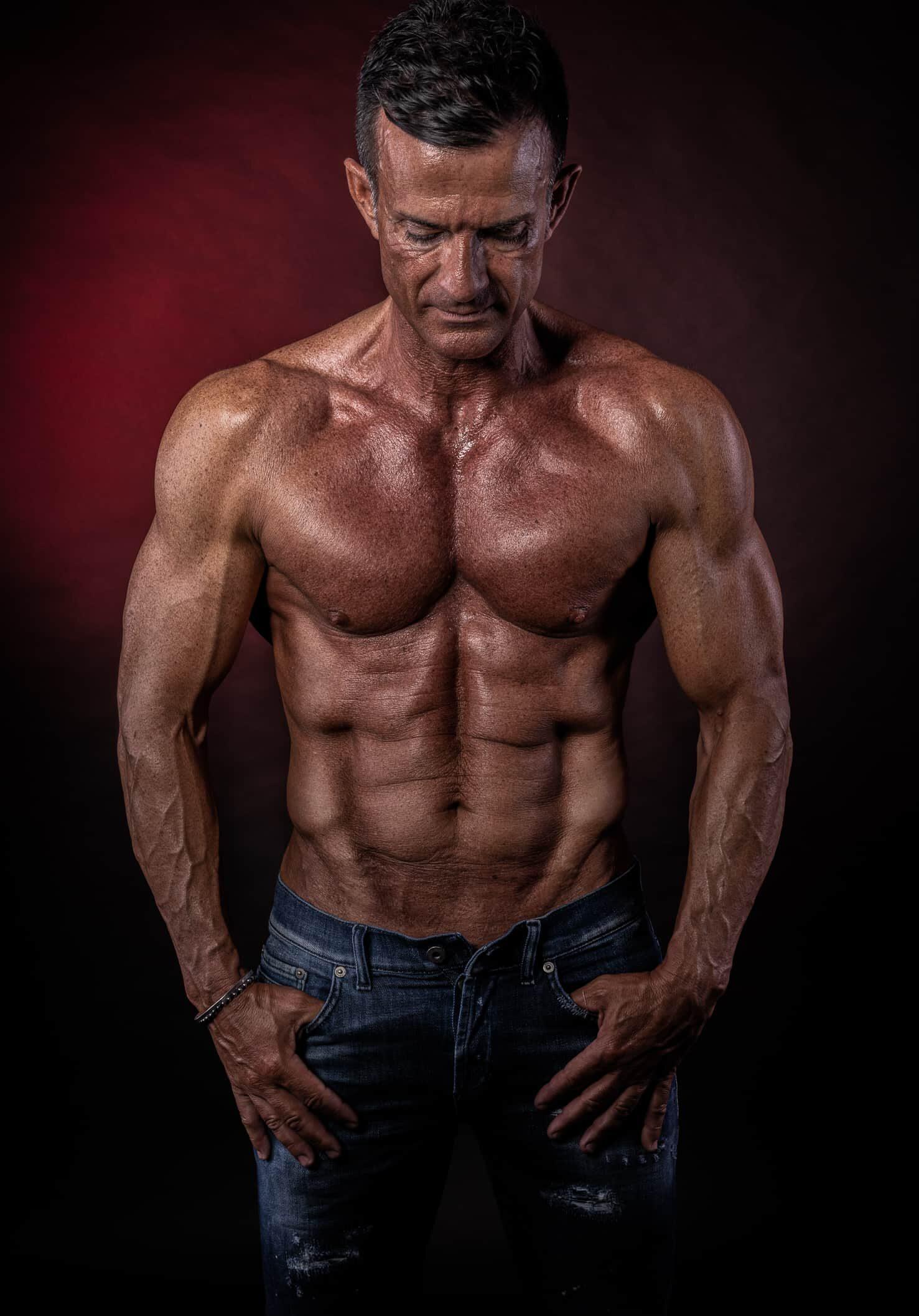fotografofitness ragazzo muscoloso a torso nudo con blue jeans servizio fotografico in studio con sfondo rosso