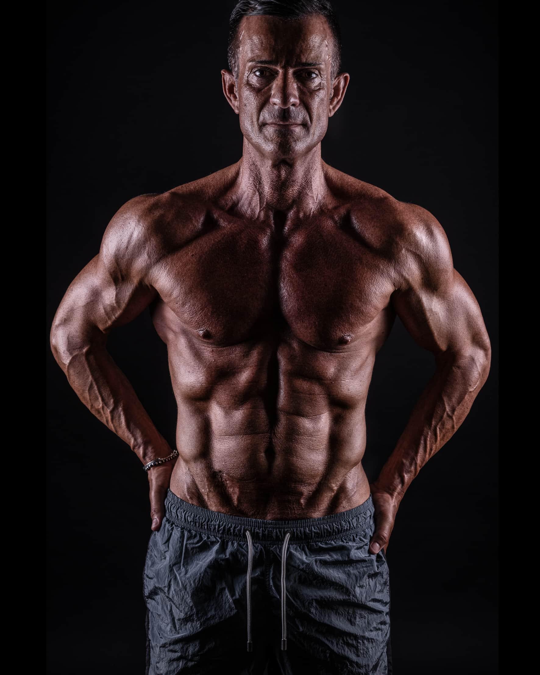 fotografofitness studio fotografico ragazzo con busto muscoloso e pantaloncini su sfondo nero