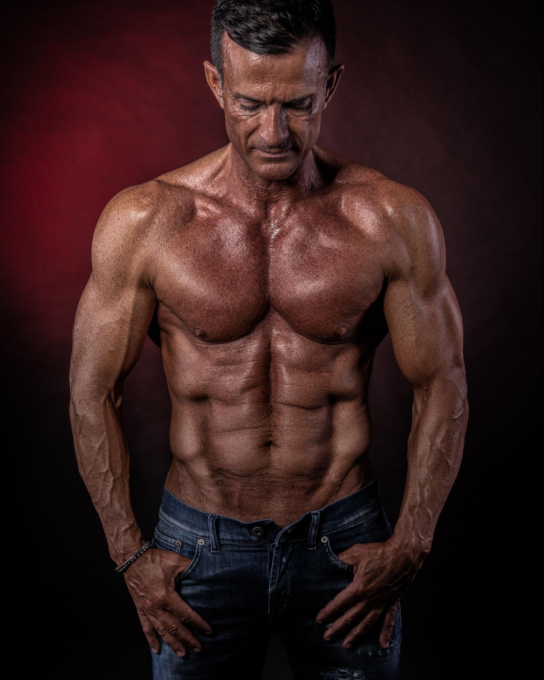 fotografo fitness servizio fotografico in studio con sfondo rosso e ragazzo muscoloso a torso nudo con addominale scolpito e blue jeans
