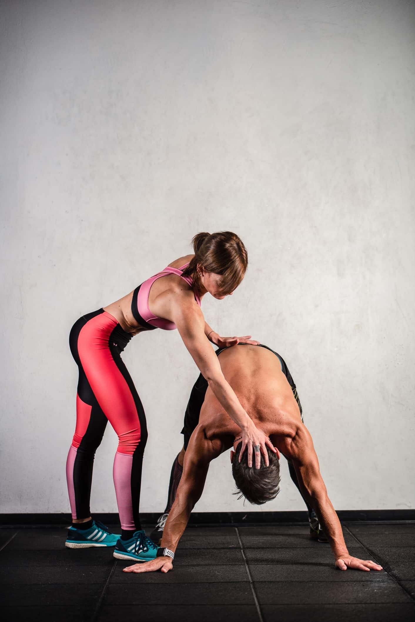personal trainer di milano con pantaloni rossi e top nero durante una sessione di personal training con ragazzo a torso nudo