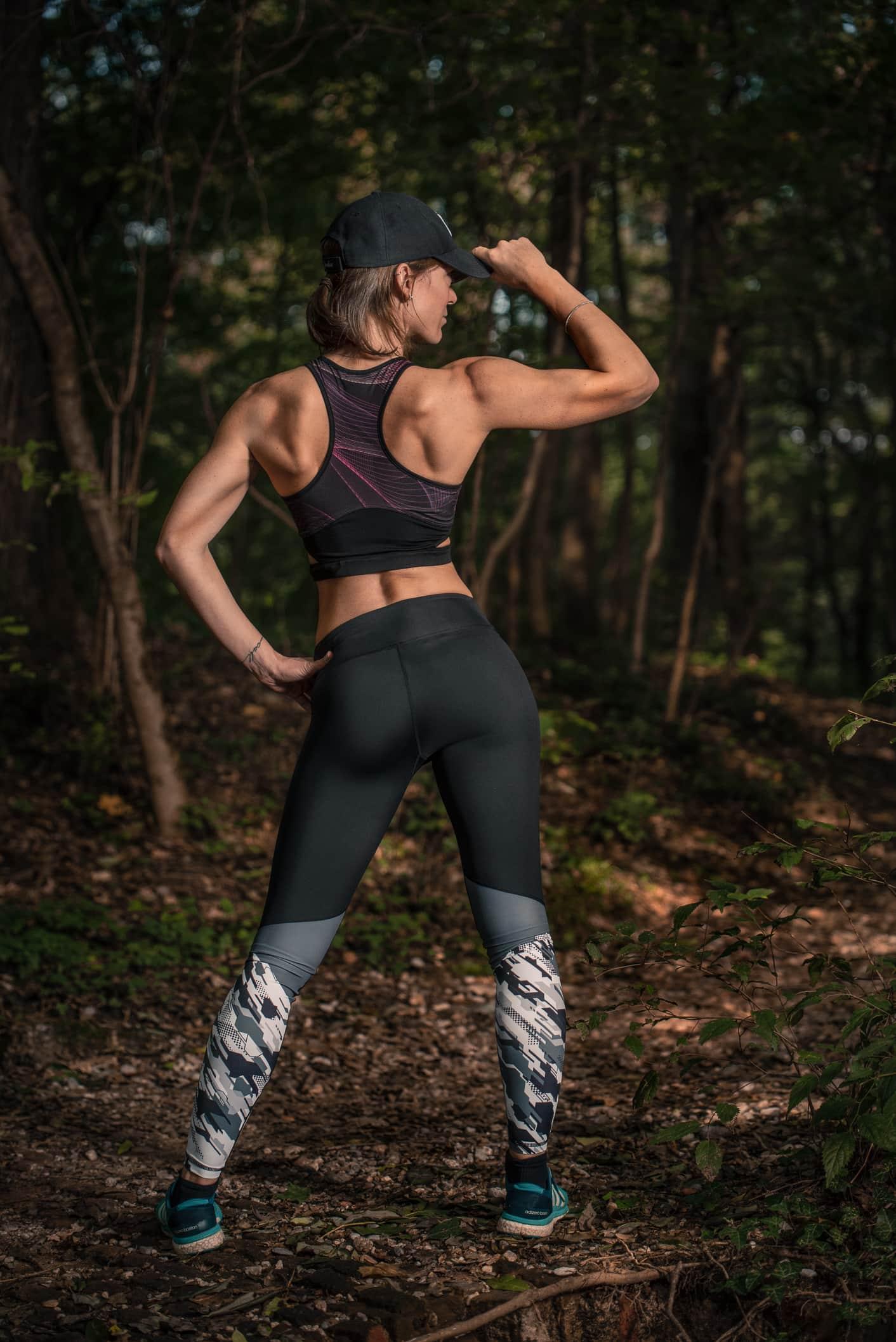 ragazza di schiena con outfit sportivo nel parco di monza tiene con la mano destra un cappellino
