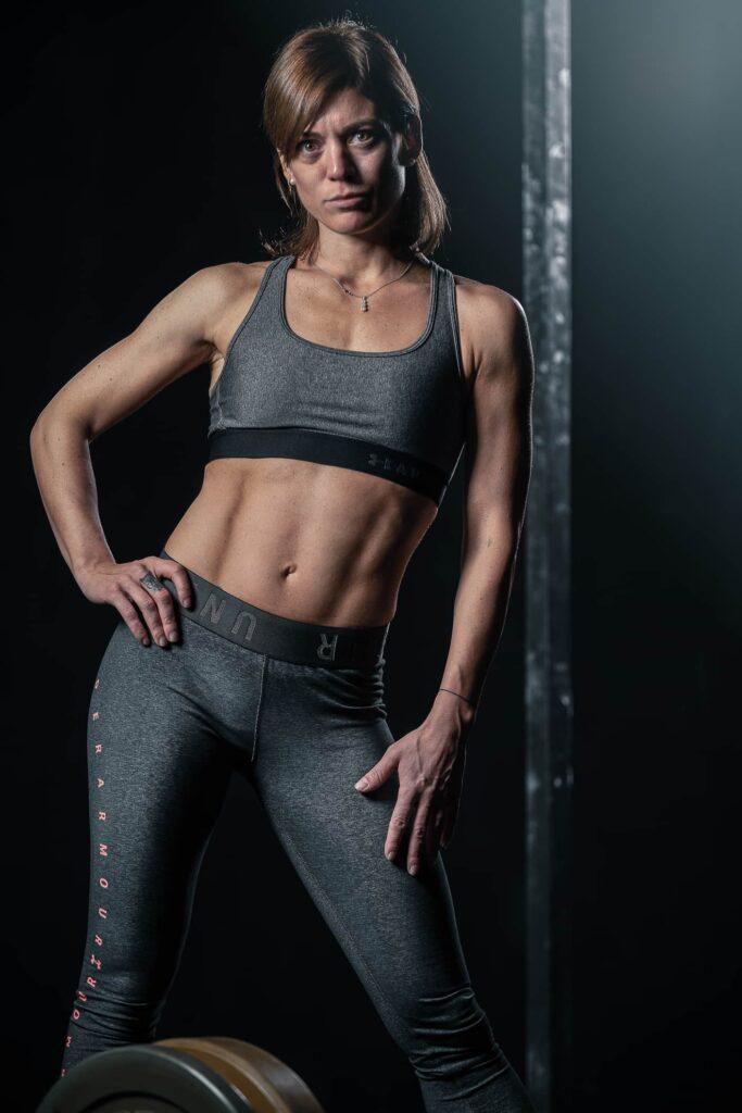 ritratto ragazza personal trainer milano in palestra con top e pantaloni grigi addominale scolpito fotografofitness