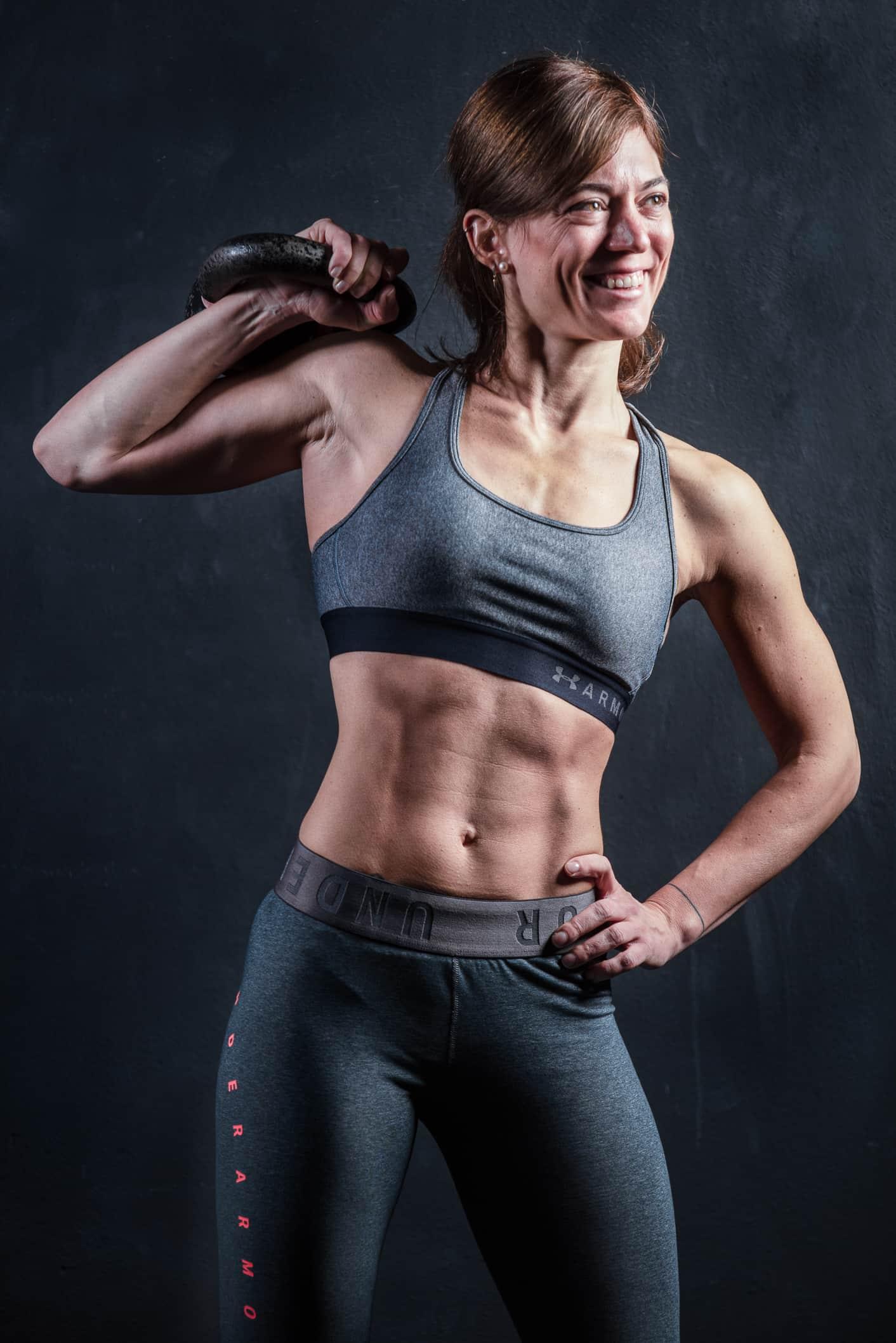 fotografofitness ragazza personal trainer sorridente con addome scolpito mentre tiene in mano un kettlebell