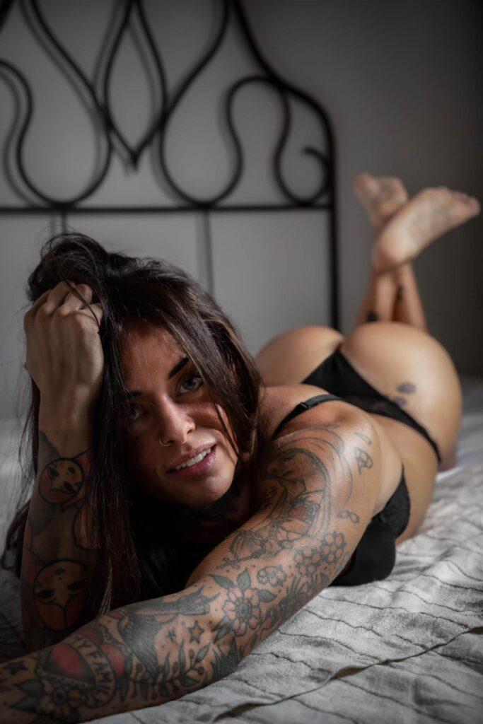 fotografo boudoir ragazza in intimo nero distesa sul letto con testiera in ferro battuto